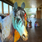 A statue of a painted horse stands near the group of children during Tidbit Tuesday at the Sheridan County Museum. Rodeo was the theme this month; the children decorated paper cowboy boots t ...