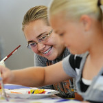 Fourteen-year-old Emma Manor, left, watches her sister Sarah Manor, 11, paint on a board during Kids' Art Camp Tuesday at Sagebrush Community Art Center inside the historic Train Depot. Th ...