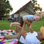 Two-year-old Henry Szewc laughs as Jason Szewc lifts him during the Concert in the Park performance by the Sheridan Concert Band Tuesday evening at Kendrick Park. The Sheridan Press|Justin S ...