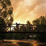 A couple of concertgoers cross the bridge over the Big Goose Creek as the sunset illuminates the sky Tuesday night at Kendrick Park. The Sheridan Press|Justin Sheely.