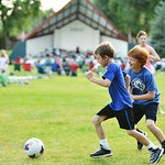 Eight-year-old Bridger Mortensen, left, and brother Brennan Mortensen, 10, play soccer with friends on the far side of the field during the Concert in the Park performance by the Sheridan Co ...