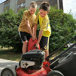 Twelve-year-old Caden Holzermer, left, and James Holst, 9, pour gasoline into a lawnmower Tuesday afternoon in front of the Sheridan Square apartment building on Smith Street. The youth star ...