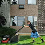 "Ten-year-old Brady Holzemer pushes a lawnmower in front of the Sheridan Square apartment building on Smith Street. Holzemer and his friends started their business this summer ""We are Mower ..."