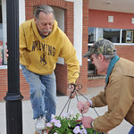Steve Kuzara, left, and Chris Schock, with RENEW, lift up a basket Saturday on Grinnell Street by City Hall. The DSA had 30 volunteers to help prepare and hang flowering baskets in downtown  ...