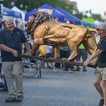 Justin Sheely | The Sheridan Press Sheridan Lions Club member Jim Rapp, left, and Ranchester Mayor Peter Clark carry a lion the the Lions Club table during the first Third Thursday street fe ...