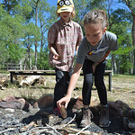 Justin Sheely | The Sheridan Press Eight-year-old Cierra Maher, left, and Sydney Herrigel, 9, place pine cones to start a campfire during the Girl Scouts' Camp Rowena Wednesday at the Poul ...