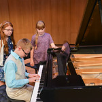 Justin Sheely | The Sheridan Press Woodland Park fifth-grader Tanner Green plays on the concert piano as Amy Peldo, left, and Graceie Hanson watch during the Composers' Concert Wednesday i ...