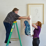 Justin Sheely | The Sheridan Press Sheridan College art students Diana Goodrich, left, and Rebekah Blommel hang up art for the student art gallery Wednesday at the Whitney Center for the Art ...