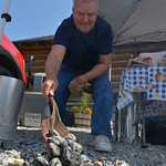 Justin Sheely | The Sheridan Press John Sarokon of Story adds coals to the fire pit for the Dutch Oven Cook-off during Story Days Friday at the Story Women's Club. Entrants compete in two  ...