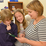 Justin Sheely | The Sheridan Press Middle schoolers Myra Fuhrman, left, and Torance Sorenson look at a student's collage project with after school teacher Emily Swinyer during the after sc ...
