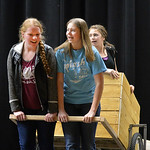 "Justin Sheely | The Sheridan Press Seniors Emma Balstad, left, and Hannah Johnston pull a cart with sophomore Holly Hutchinson during a rehearsal for ""The Great Tie Flume"" Tuesday at Ton ..."