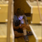 Justin Sheely | The Sheridan Press A girl looks at her phone under the bleachers during the Broncs basketball game Friday at Sheridan High School.