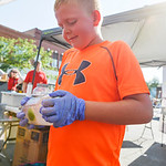 Nine-year-old Mason Mayfield shakes up a jar of lemonade for the Adams Family Concession during the Farmers Market Thursday on Grinnell Plaza.
