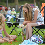 Justin Sheely | The Sheridan Press Kayla Bowie, left, and Brooklyn Bowie, 14, keep their three-month-old Yellow Labrador occupied during Concerts in the Park Tuesday evening at Kendrick Park ...
