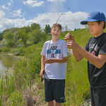 Justin Sheely | The Sheridan Press Twelve-year-old Chase Bales laughs as Cade Butler removes a water plant he caught on the line at Sam Mavrakis Pond on Wednesday. The popular fishing pond i ...