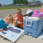 Justin Sheely | The Sheridan Press Nine-year-old Marra Donahue, left, and Mason Cooley, 7, write on a whiteboard for their lemonade stand Saturday afternoon in a residential area of Sheridan ...