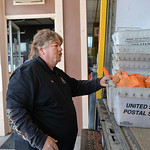 Justin Sheely | The Sheridan Press Food Bank volunteer Mike Voogd carries donations collected by the US Post Office to the end of the truck Friday at the People Assistance Food Bank. The US  ...