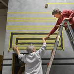 "Justin Sheely | The Sheridan Press Artist Pat Trout, left, reaches for a pencil offered by fellow artist Paulette Kucera as they paint the stage sets for the upcoming Wyo Theater Gala: ""Le ..."