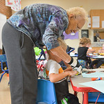 Justin Sheely | The Sheridan Press Foster Grandparent volunteer Halen Gold, age 90, helps a preschooler with his scissors during an art activity Friday morning at the YMCA Preschool.