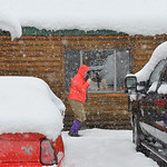 Justin Sheely | The Sheridan Press A person walks past parked vehicles as snow falls at Bear Lodge Resort Saturday afternoon in the Bighorn National Forest. Heavy snow caused trees to bring  ...