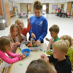 Justin Sheely | The Sheridan Press Kids swarm around a table with beads and string for a Jamaican bracelet craft activity during the after school program at the YMCA Tuesday.