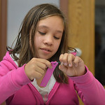 Justin Sheely | The Sheridan Press Third-grader Juliann Amende ties a string for a Jamaican bracelet craft activity during the after school program at the YMCA Tuesday.