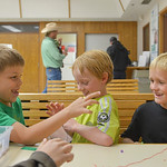 Justin Sheely | The Sheridan Press First graders, from left, Adam Bauers, Kal Condos and Cooper Berry distract each while in a Jamaican bracelet craft activity during the after school progra ...