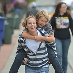 Justin Sheely | The Sheridan Press Twelve-year-old Derrick Bates gets a piggy-back ride from Desiree Fresorger during the final Third Thursday Street Festival on Main Street.