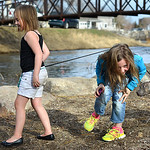 Justin Sheely | The Sheridan Press Nine-year-old Gabby Springsteen ducks under the leash as Jayda Kelly, 8, leads her young pitbull named Poseidon by the Big Goose Creek Wednesday at Kendric ...
