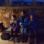 Justin Sheely | The Sheridan Press Guests, from left, Ever Poll, 4, Nichole Poll and Vella Poll, 8, sit outside to enjoy their treats during the 5th annual Ucross Christmas Celebration at th ...