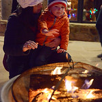 Justin Sheely   The Sheridan Press Jennifer Graslie and her son Caleb Graslie, 3, warm by the fire during the 5th annual Ucross Christmas Celebration at the Raymond Plank Creative Center at  ...