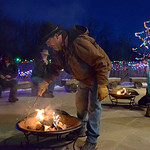 Justin Sheely   The Sheridan Press Ucross employee Marty Jelly puts a log on the fire during the 5th annual Ucross Christmas Celebration at the Raymond Plank Creative Center at Ucross Saturd ...