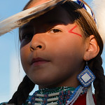 Justin Sheely | The Sheridan Press A young dancer shields her face during the grand entry powwow Saturday evening during Crow Fair at Crow Agency, Montana. Crow Fair started in 1904 and is c ...