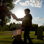 Justin Sheely | The Sheridan Press Six-year-old Hunter Bailey carries flags to grave sites with empty flag holders during morning decorating on Memorial Day at the Sheridan Municipal Cemeter ...