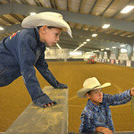 Justin Sheely | The Sheridan Press Eleven-year-old Karson Campbell, left, and Nicholas Three Irons, 9, hangout by the bucking chutes during the performance of the Northern Plains Indian Rode ...