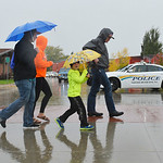 Justin Sheely | The Sheridan Press A family crosses the street under pouring rain during the Out of the Darkness suicide prevention walk Saturday in Sheridan. The event is held annually in S ...