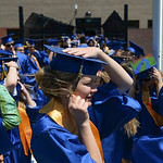 Justin Sheely | The Sheridan Press Brenna Kysar holds her hat against the wind as graduates line up outside the field during the 2017 graduation ceremony Saturday at Sheridan High School.