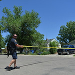 Justin Sheely | The Sheridan Press A Sheridan Police officer pulls tape across the street near the scene where a man reportedly fired guns in random directions Wednesday afternoon on Spauldi ...