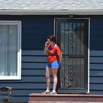 Justin Sheely | The Sheridan Press A resident looks out from her front door as authorities respond to a shooting nearby Wednesday afternoon on Spaulding Street. A man was arrested Wednesday  ...