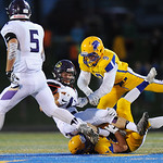 Justin Sheely | The Sheridan Press Broncs' Hayden Hastings, top, and Kyle Custis tackle Camels' running back Austin Clemetson during the rivalry game against Gillette Friday night at Sco ...