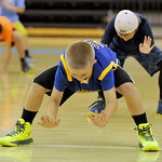 Mark Gilbert smacks the floor at the start of a defensive-slide drill at the Sheridan College summer boys basketball camp on Tuesday, June 14 at the Bruce Hoffman Golden Dome. Mike Pruden |  ...