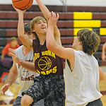Robert Watson, center, twists his body to get a shot up over two defenders during practice on Wednesday, Nov. 30 at Big Horn High School. Mike Pruden | The Sheridan Press